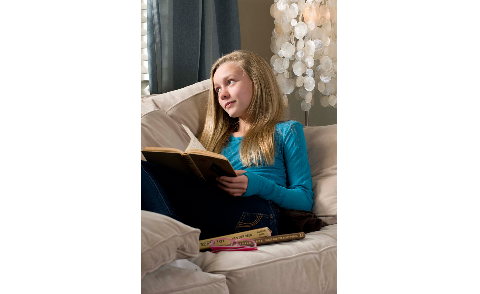 girl tween reading and daydreaming at window